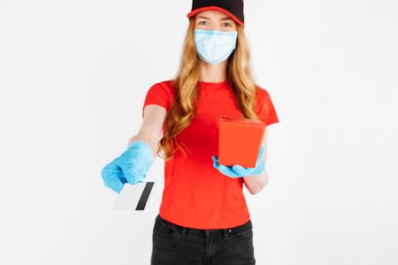 A uniformed courier, wearing rubber gloves and a medical mask, holds a paper box of food and a credit card for non-cash payment on a white background. coronavirus, quarantine