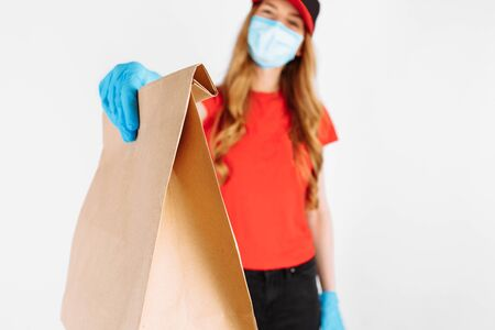 A courier in a red uniform, wearing rubber gloves and a medical mask holds a paper bag with food isolated on a white background. A female employee works as a courier. Service concept. Home delivery, quarantine, coronavirus