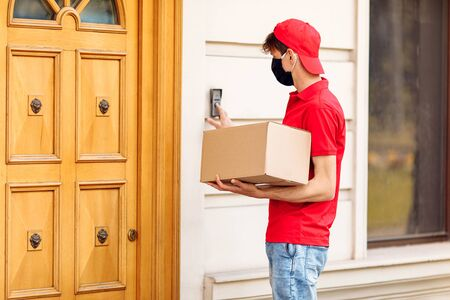 A courier in a protective medical mask with boxes in his hands delivers parcels. Service delivery in terms of quarantine, pandemic coronavirus