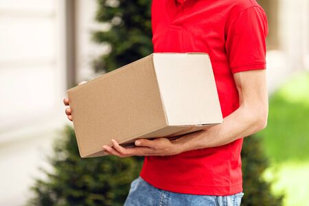 Courier with parcels in hand in the open air