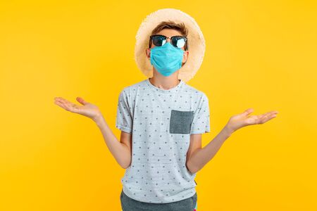 unsure doubting teenager in a protective medical mask on his face, spreads his hands on an isolated yellow background