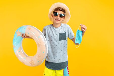 smiling happy teenage boy in a summer hat and sunglasses, holding a protective medical mask and a sea swimming circle on an isolated yellow background