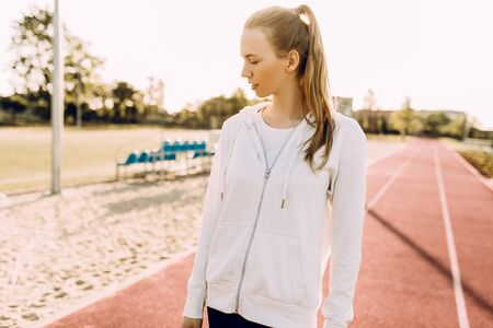 Attractive athletic girl in sportswear, at the stadium against the background of dawn