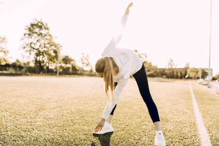 Attractive slim athletic woman doing stretching exercises in the open air. Sports, coronavirus, quarantine