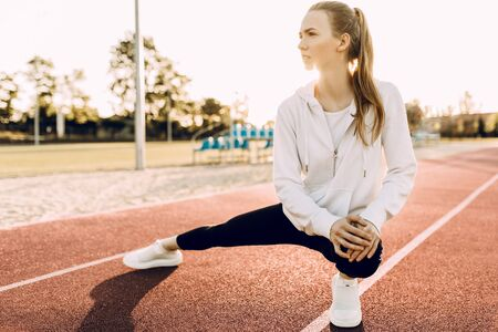 Athletic beautiful woman in sportswear outdoors doing stretching exercises