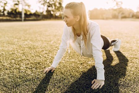 Attractive sportswoman makes a plank, in the fresh air