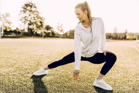 Slender girl athlete in sports clothes, doing stretching in the morning at dawn Stock Photo