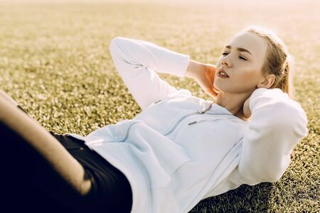 Beautiful young fitness woman doing abs exercises while lying in the stadium Stock Photo