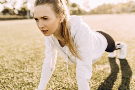 Perfect Board. Young beautiful woman in sportswear doing a plank while standing outdoors