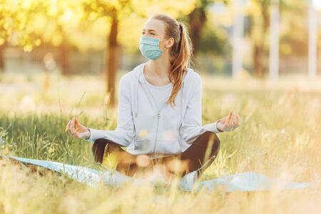 girl in a medical protective mask meditates in the Lotus position on the green grass at dawn. Healthy lifestyle and relaxation.
