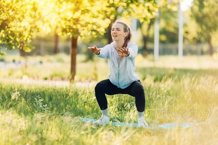 Wysportowana młoda kobieta uprawiająca sport w parku rano, trening kobiet na macie do jogi