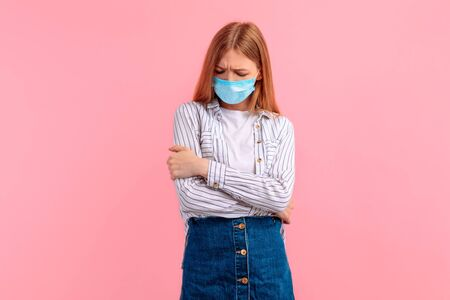 sad, offended young woman in a medical protective mask on her face looks with a disappointed expression, an offended grimace. on a pink background Фото со стока