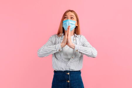 pleading young woman, wearing a medical protective mask on her face, prays with her hands clasped in prayer against a pink background Фото со стока