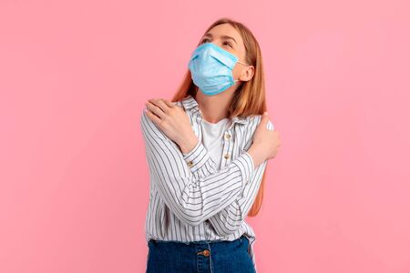young attractive woman in a medical protective mask holding herself in an embrace, against an isolated pink background. Love yourself