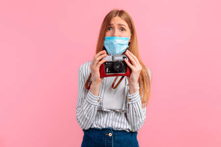 Happy young woman in a medical mask on her face, gives a thumbs up and smiles cheerfully, I like it, on a pink background