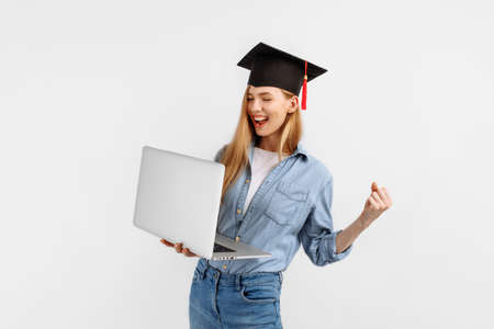 Happy excited graduate girl in a graduation cap on her head using a laptop and showing a winning gesture while standing on a white background. Graduation, distance learning Foto de archivo