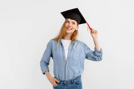 pensive, dreamy graduate with a graduation cap on her head, on an isolated white background. Standard-Bild