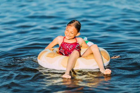 Happy child on an inflatable circle floating on the sea, Summer holidays with children. Swimming equipment and clothing for children. A little girl is floating on an inflatable circle