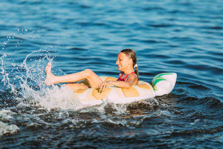 Happy child on an inflatable circle floating on the sea, Summer holidays with children. Swimming equipment and clothing for children.