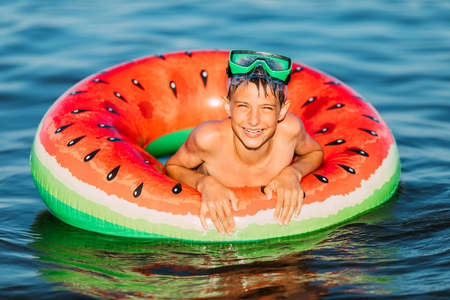 happy child on an inflatable circle swims on the sea, in the summer resting on the sea. A little boy has fun and swims on an inflatable circle