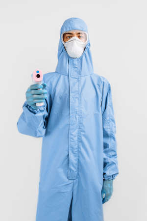 male doctor in a protective suit from the coronavirus, a medical mask glasses and gloves, uses an infrared non-contact thermometer gun to check body temperature for symptoms of the covid-19 virus, on an isolated white background