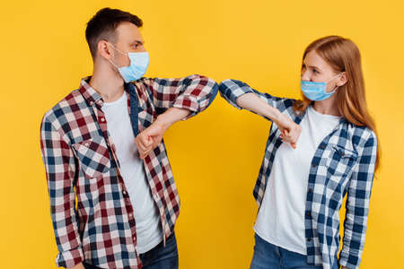 Portrait of a man and woman in plaid shirts and medical protective masks greeting each other with their elbows, on an isolated yellow background