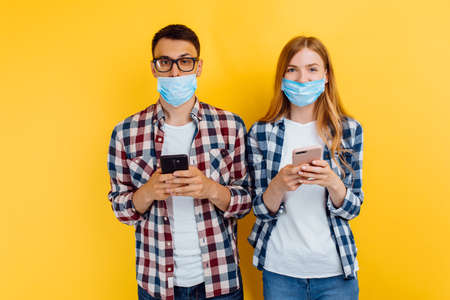 Happy guy and girl in plaid shirts and medical masks on their faces using mobile phones on a yellow background Reklamní fotografie