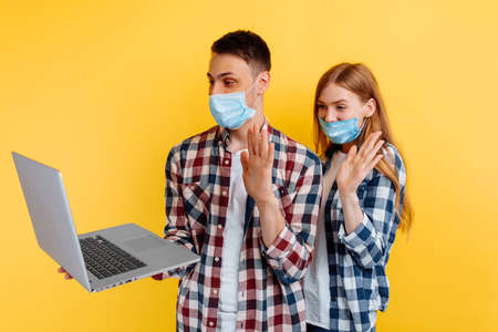 cheerful young couple, a man and a woman in plaid shirts and medical protective masks on their faces, are working on a laptop computer and are greeted by looking at a laptop screen, on a yellow background