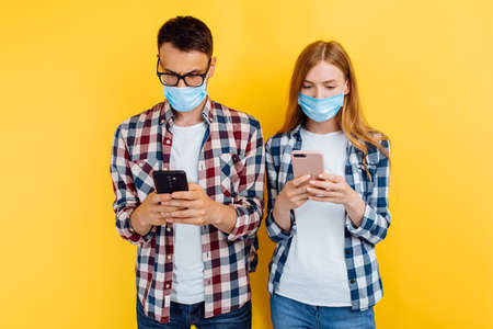 young couple, a boy and a girl in checked shirts and medical protective masks, using mobile phones, isolated on a yellow background