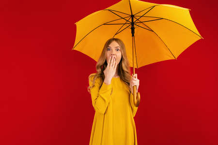 Shocked beautiful young woman, with a yellow umbrella on a red background, autumn concept Reklamní fotografie