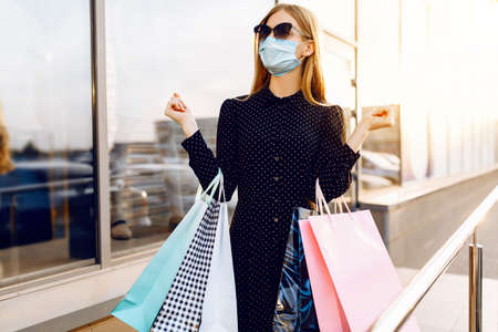 young woman in sunglasses and a medical protective mask on her face, with shopping bags, in the city against the background of a shopping center