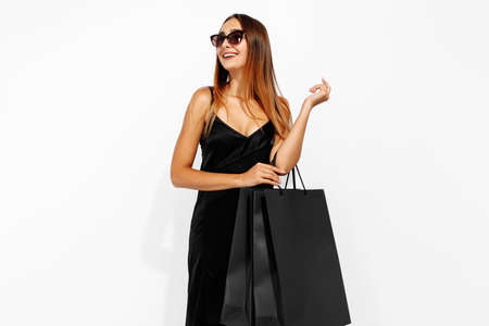 young woman in black dress and sunglasses, with shopping bags on a white background, shopping concept, Black Friday