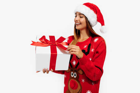 Cheerful young woman in a Christmas sweater and Santa Claus hat, with a gift on a white background, the concept of Christmas, New Year
