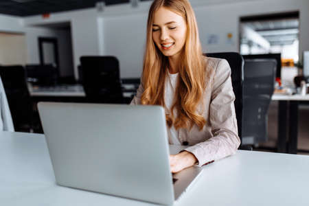 Business young woman working with laptop sitting at table in office