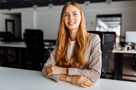 business young woman sitting at work desk in office