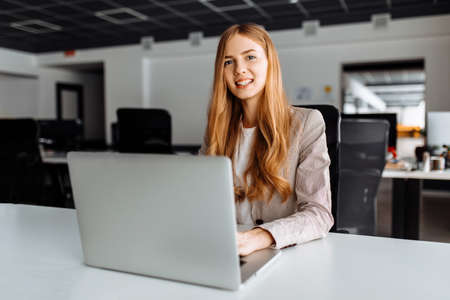 Business young woman sitting at table with laptop in office, business concept