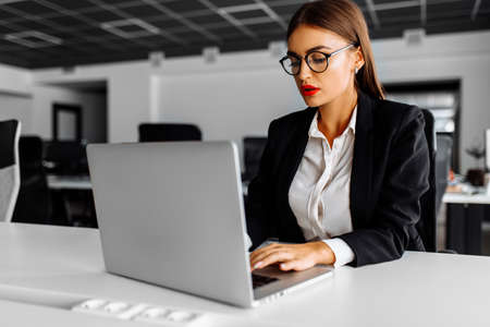 young business woman working with laptop in her office, business concept