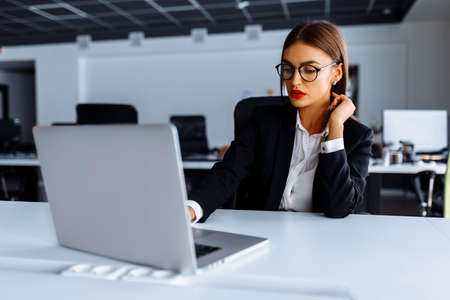 Attractive young business woman working with laptop in her office, business concept