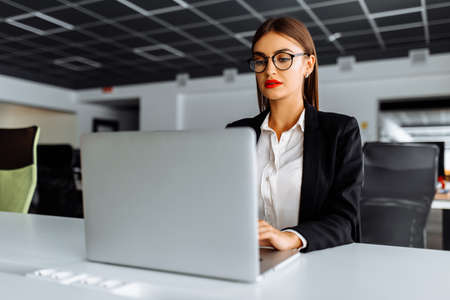 Attractive young business woman working with laptop in her office 免版税图像