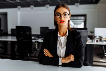Attractive young business woman sitting at work table in office, business, success concept