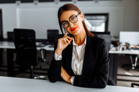 Attractive young business woman sitting at work table in office, business, success concept 免版税图像