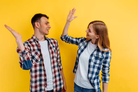 Portrait of excited young couple giving high five on yellow background