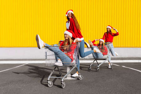 Young happy friends in Christmas sweaters and Santa Claus hats are having fun on a shopping trolley, against the background of a yellow wall of a shopping center, shopping concept, Christmas, New Year
