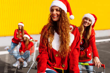 Happy young women friends in christmas sweaters and santa claus hats celebrate new year and ride trolleys against yellow wall background