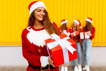 Beautiful smiling young woman wearing santa claus hat with christmas present standing against background of happy friends celebrating christmas