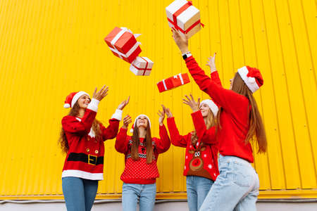 Excited, rejoicing group of friends wearing santa claus hats having fun and tossing christmas presents on yellow wall