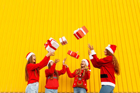 Happy rejoicing girlfriends in santa claus hats having fun and throwing christmas gifts while standing against yellow wall