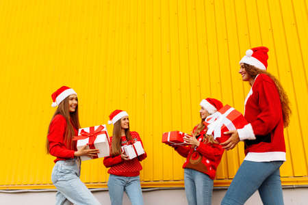 Happy attractive rejoicing girlfriends in santa claus hats celebrate new year with christmas gifts