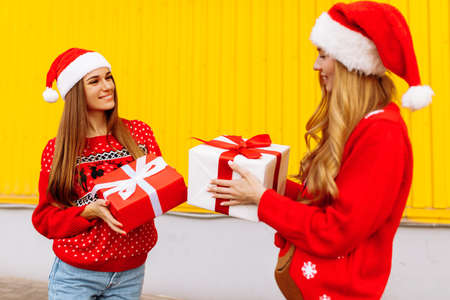 Two smiling young women in red sweaters and santa claus hats give each other christmas gifts while standing against yellow wall