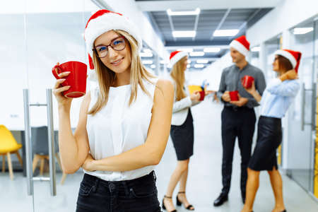 Happy young business woman in Santa Claus hat, holding a red mug, with a group of colleagues in the background, during a coffee break in the office